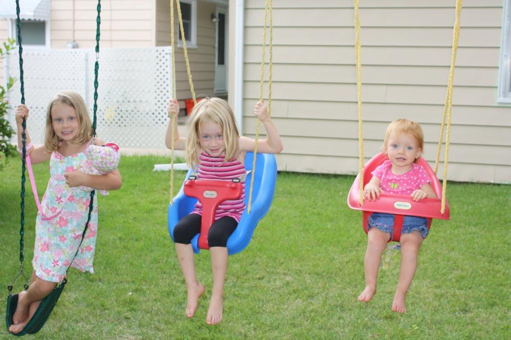 Three little monkeys swinging on a swing.
